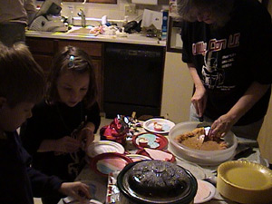 Connor Taurins and Bea Pfeiffer help Karen Peiffer serve up Bea's pumpkin pie course